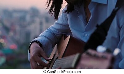 Close up of hands playing the guitar against a beautiful city background