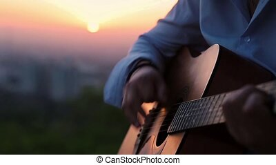 Close up of hands playing the guitar against a beautiful sunset