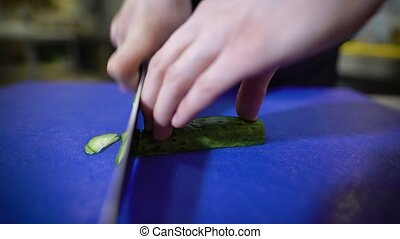 Close up of hands professionally slicing cucumber with sharp knife on blue plastic carving board. Chef in restaurant is cutting vegetables for salad.