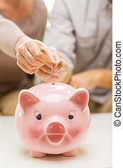 close up of hands putting coin money to piggy bank
