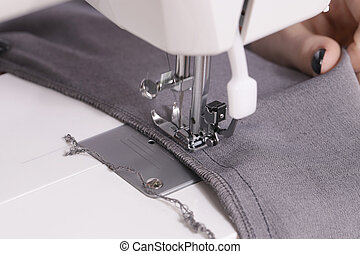 Close-up of hands sewing on machine