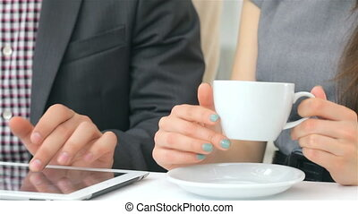 Close-up of hands show on the tablet, cups of coffee