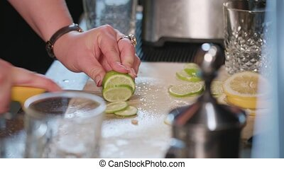 Close-up of Hands Slicing a Lime in the Kitchen