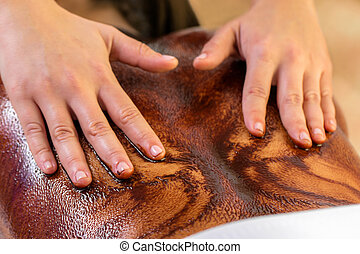 Close up of hands spreading hot chocolate on female back.