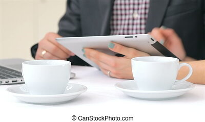 Close-up of hands, two cups of coffee in the foreground attractive business man and woman