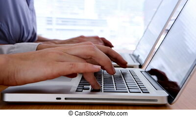 Close up of hands typing on laptop