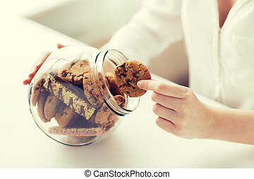 close up of hands with chocolate cookies in jar