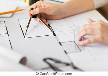 close up of hands with compass measuring blueprint -...