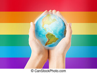 close up of hands with earth globe over rainbow