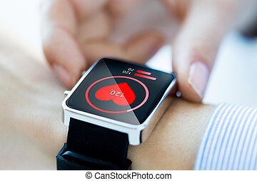 close up of hands with heart icon on smartwatch -...