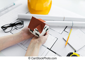 close up of hands with house model above blueprint - ...