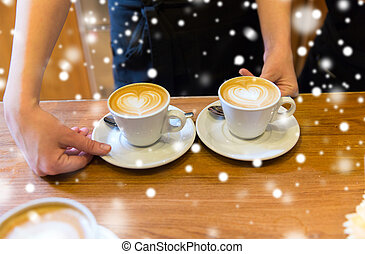 close up of hands with latte art in coffee cup
