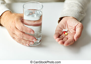 close up of hands with medicine pills and water
