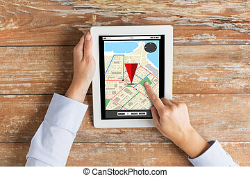 close up of hands with navigator map on tablet pc -...