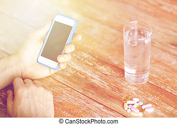 close up of hands with smartphone, pills and water