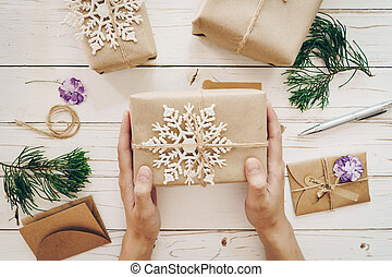 Close up of hands woman present gift box on wooden table with xmas decoration.
