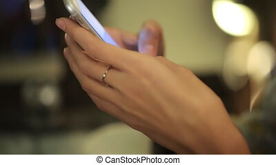 Close up of hands woman with a ring on the finger using her cell phone. indoor.He writes a message or chat with your favorite friends in social networks