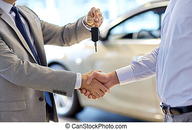 auto business, car sale, deal, gesture and people concept - close up of dealer giving key to new owner and shaking hands in auto show or salon