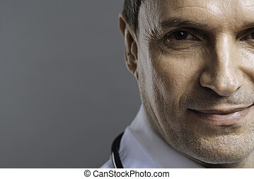 Close up of handsome doctor smiling on a grey background