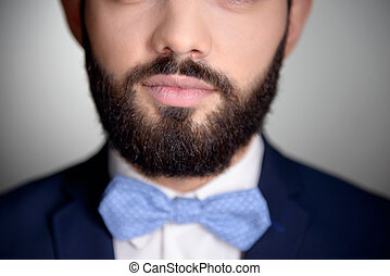 Close up of handsome man with beard and bow tie