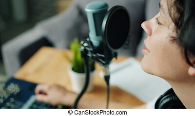 Close-up of handsome teenage boy talking in recording studio...