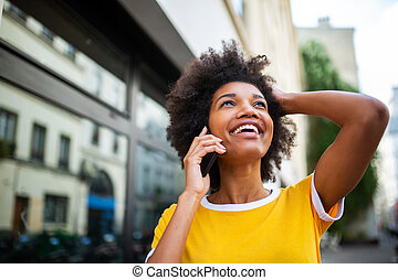 Close up of happy african american young woman talking with phone outside