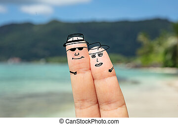 Couple Faces On Human Finger Against Blurred Beach -...