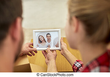 close up of happy couple looking at family photo
