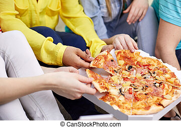 close up of happy friends eating pizza at home