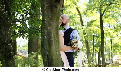 Close-up of happy groom kissing bride's forehead near old tree in the park