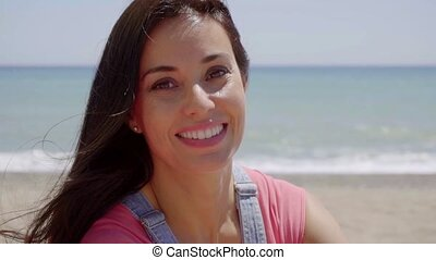 Close up of happy lady with ocean background - Close up on...