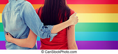 close up of happy lesbian couple hugging at home