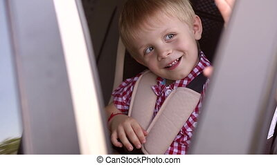 Close-up of happy little boy's face in car seat in summer. Child safety.