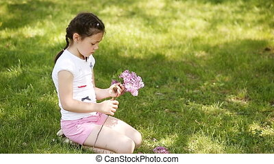 Close-up of happy little girl braiding wreath from flowers...