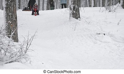 Close up of happy little girl in skiing outfit, sitting on her red sleigh and quickly sliding down from the top of the hill. Child spending her vacation together with her family in the winter forest.