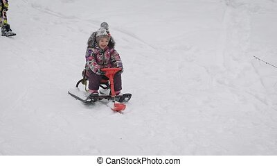 Close up of happy little girl sitting on her red sleigh and sliding down from the hill. Small princess is spending her vacation together with her family in the winter forest, riding her sled.