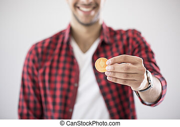 Close-up of happy man holding gold coin of ethereum