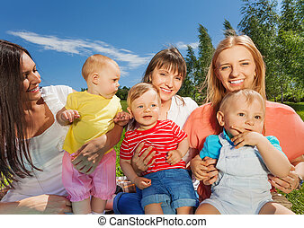 Close-up of happy mothers holding cute babies