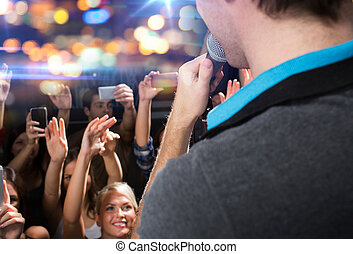 close up of happy people at concert in night club