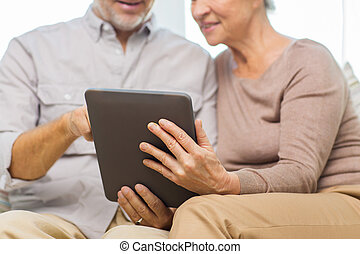 close up of happy senior couple with tablet pc - family,...