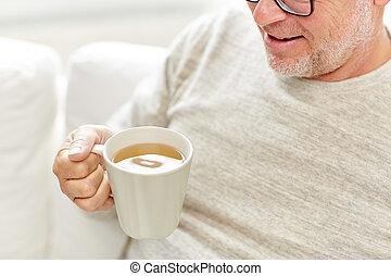 close up of happy senior man drinking tea at home