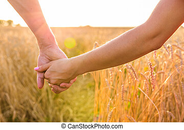 Close-up of happy young couple walking on wheat field