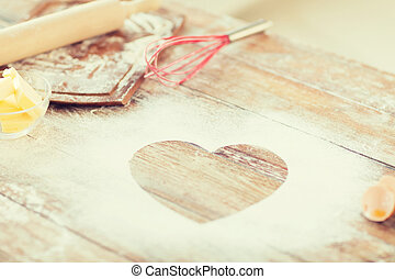 close up of heart of flour on wooden table at home - cooking...