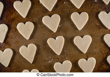 Close Up of Heart Shaped Cookie Dough on Sheet Pan