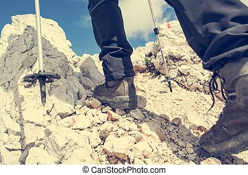 Close up of hiking shoes and trekking poles ascending a...