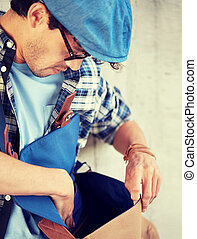 close up of hipster man looking into his bag