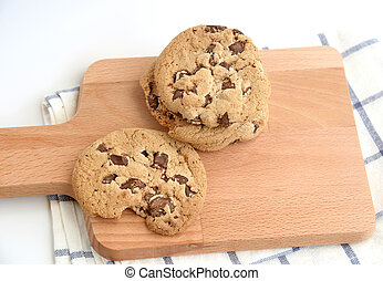close up of home made chocolate chip cookies on a wooden plate