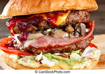 Close-up of home made tasty burgers with beef, mushrooms, bacon, and cheese on wooden table. cranberry hot sauce.
