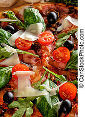 Close-up of Homemade delicious pizza with bacon, tomatoes, olives and basil.
