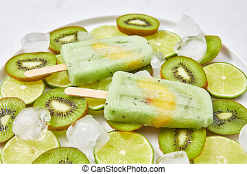 Close-up of homemade lime kiwi icy popsicle with a piece of peach in a plate with ice cubes and pieces of fruit